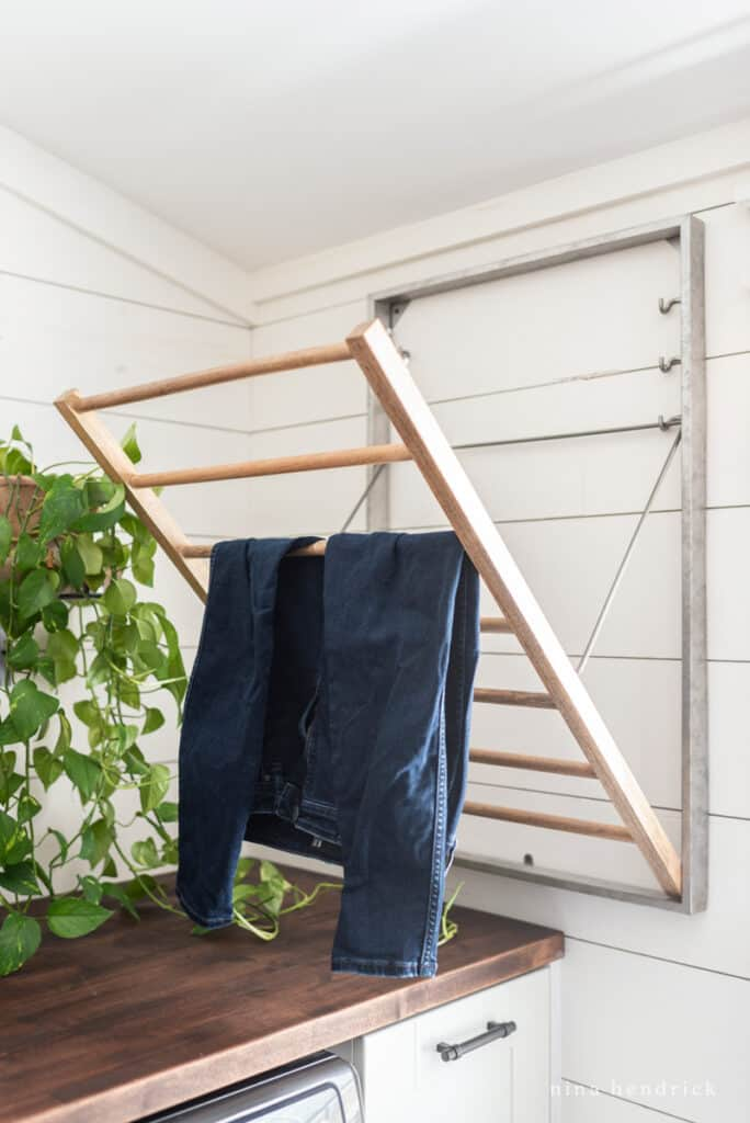 galvanized drying rack with jeans and a leafy green plant