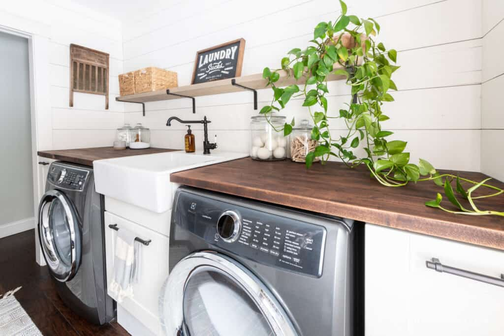 Laundry room makeover with white walls and a long trailing houseplant