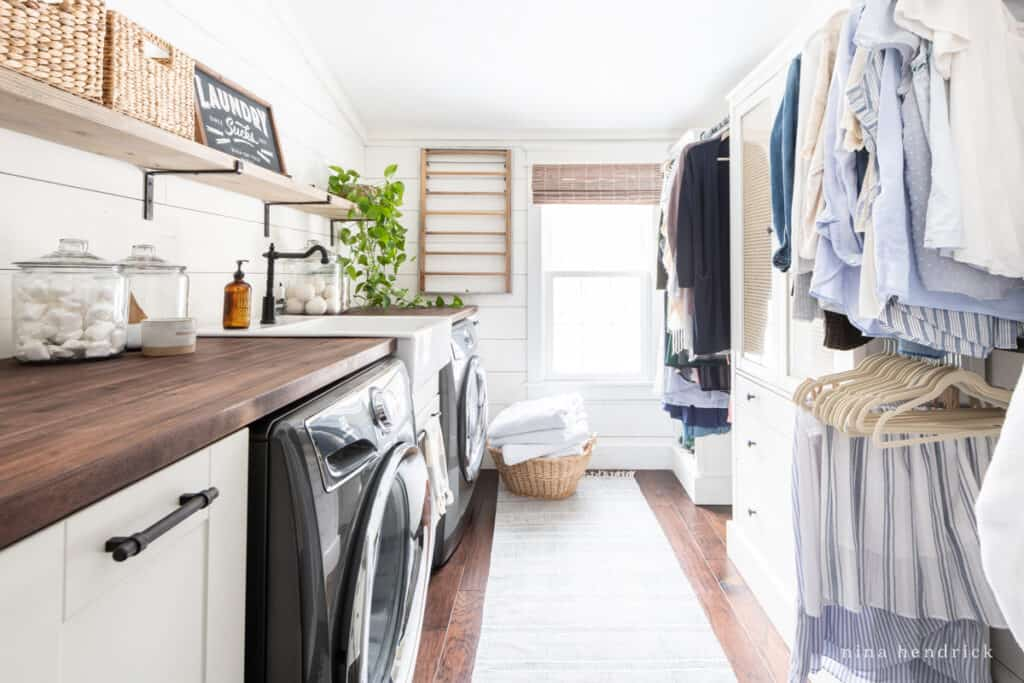 second-floor laundry room with a closet and white planked walls