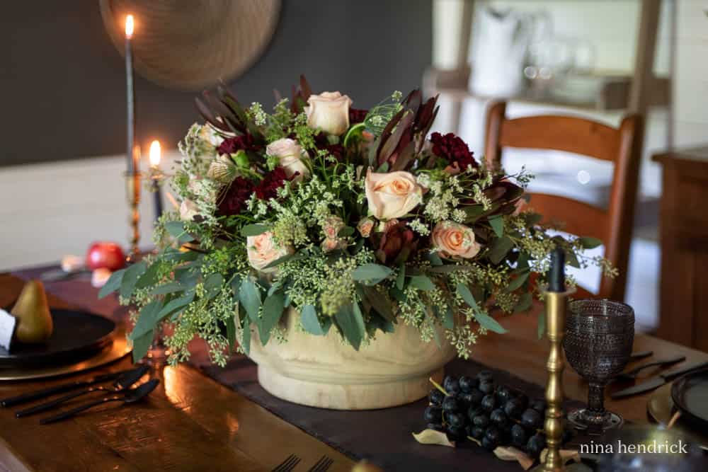 Fall floral arrangement with roses, carnations, and seeded eucalyptus.