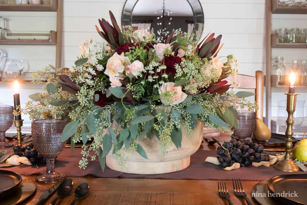 Large floral arrangement in a wooden bowl with fall colors