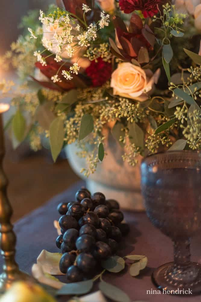 grapes next to floral arrangement
