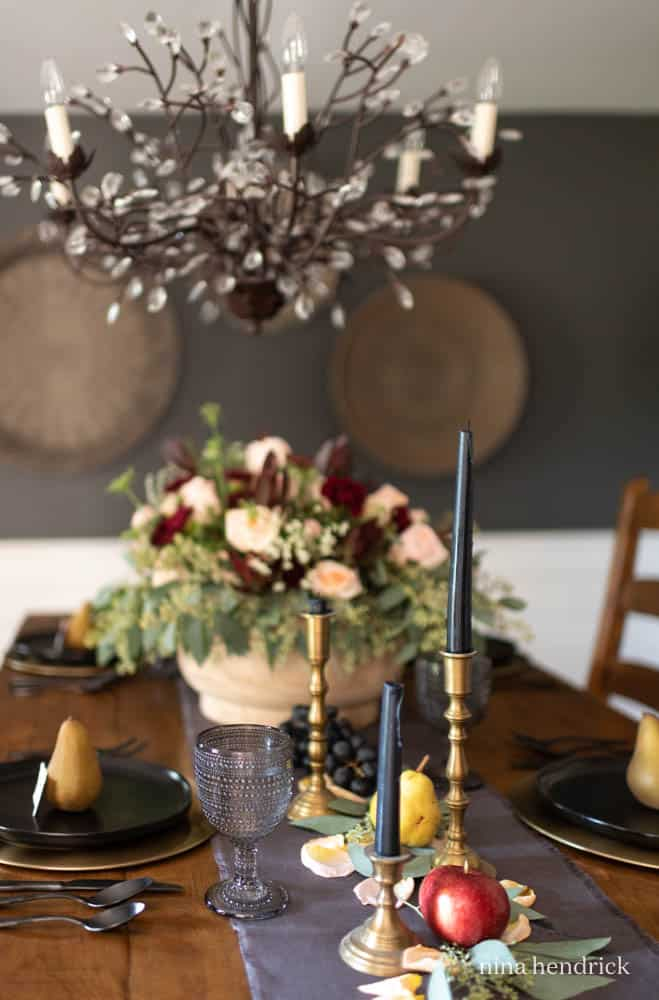 Moody Fall Tablescape with brass candlesticks, apples, and pears.