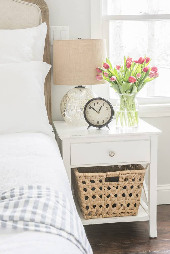 Practing a morning routine by getting up early, alarm clock on nightstand with flowers