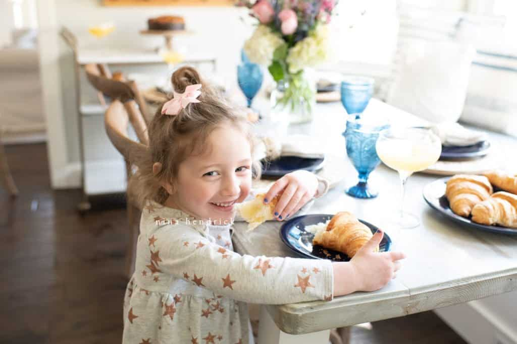 Little girl eating a croissant at Mother's Day Brunch.