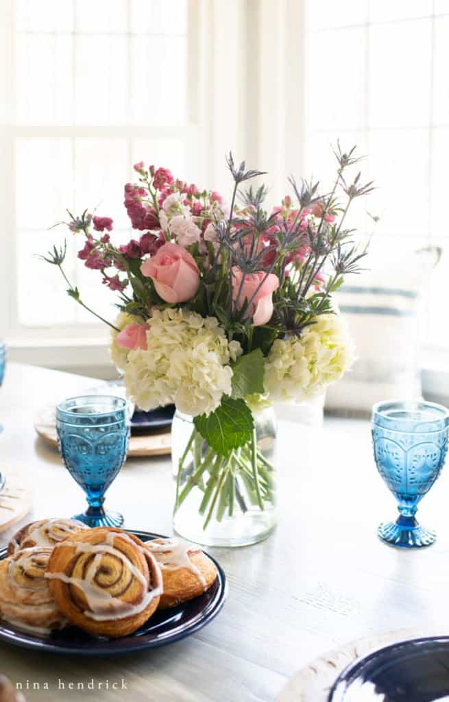 floral arrangement and a plate of breakfast pastries