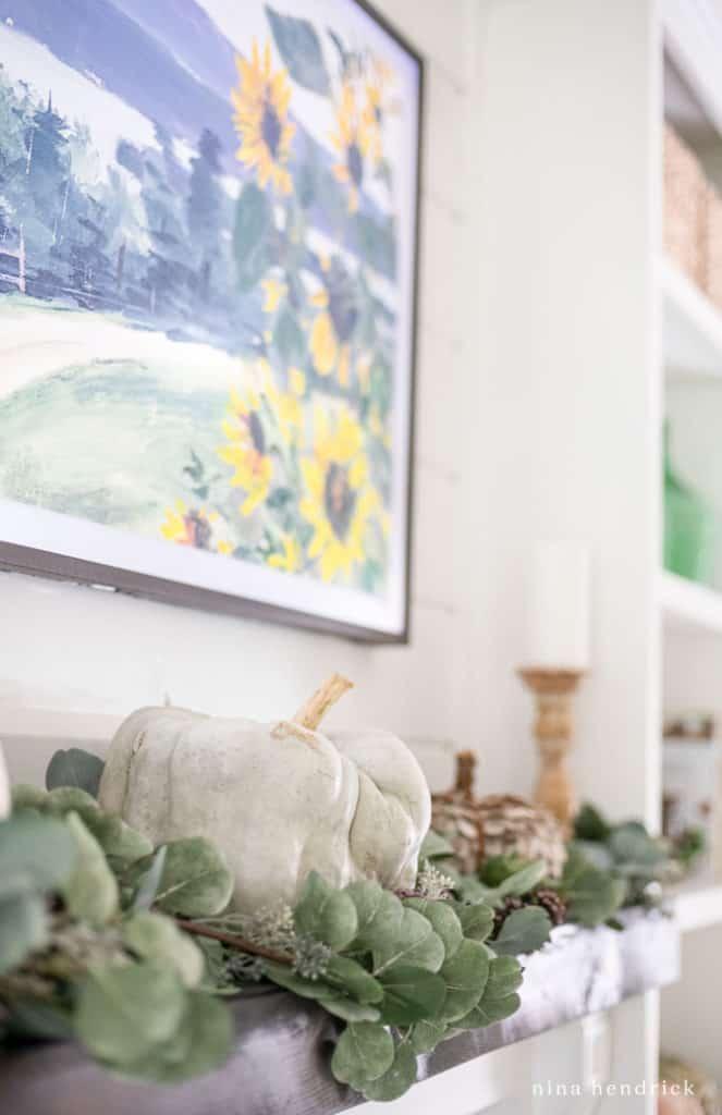green heirloom pumpkin and greenery on the mantel