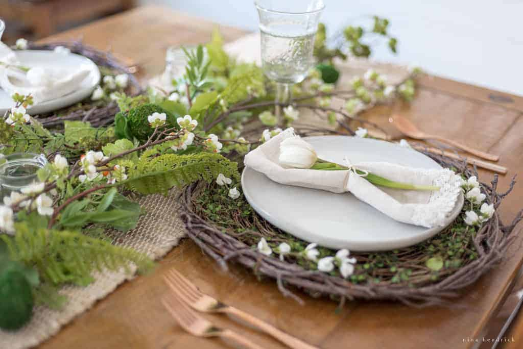 Natural Spring Tablescape | Recreate this natural spring tablescape and dining room vignette for Easter using ferns, moss, eggs, flowers, and flowering branches!