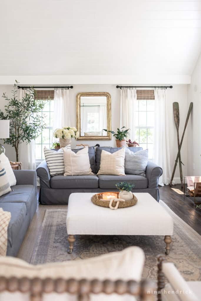 Gray Slipcovered sofas with neutral pillows and oar decor