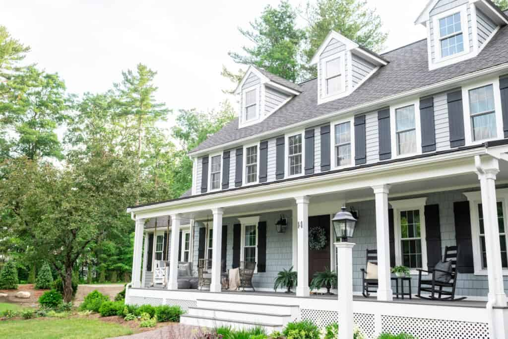 New England Colonial with three dormers and black shutters with farmer's porch