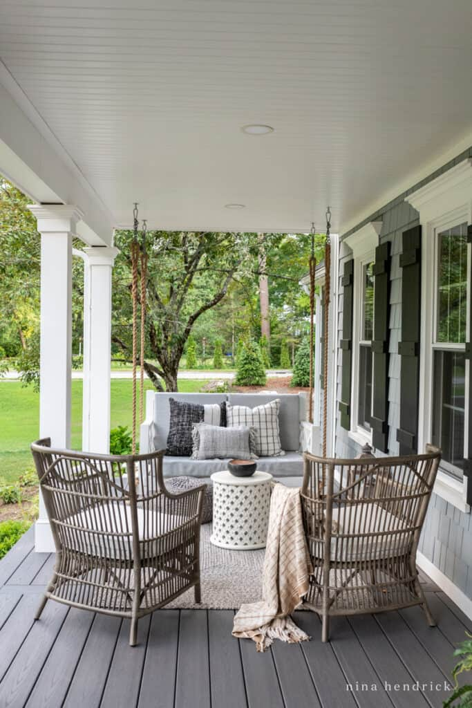 Farmer's porch with gray wicker chairs and bed swing to make up a relaxing conversation area