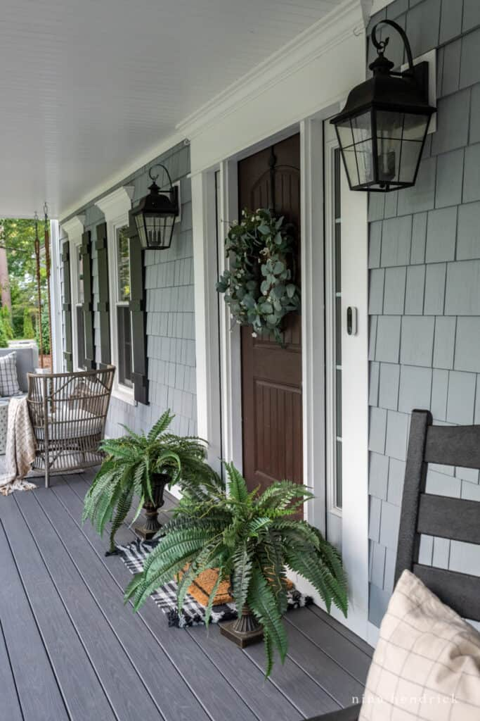 Wood look front door with faux ferns and a wreath