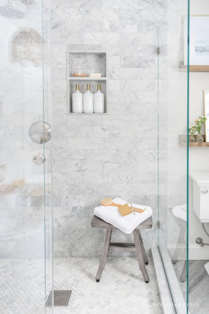 Carrara marble tiled shower with a glass surround