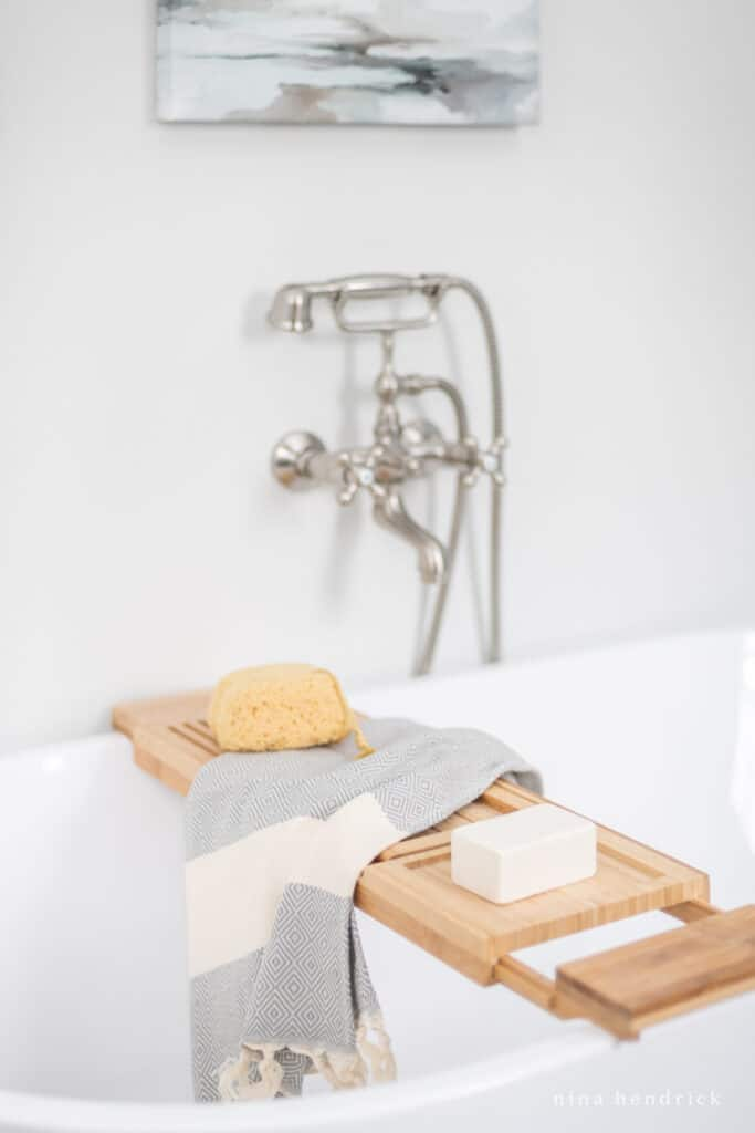 wood tub tray with sea sponge and rustic soap on a turkish towel