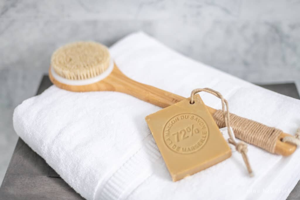 wood scrub brush on a towel with french soap