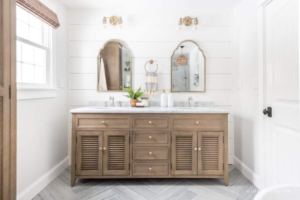 Primary bathroom remodel with herringbone floors and planked walls