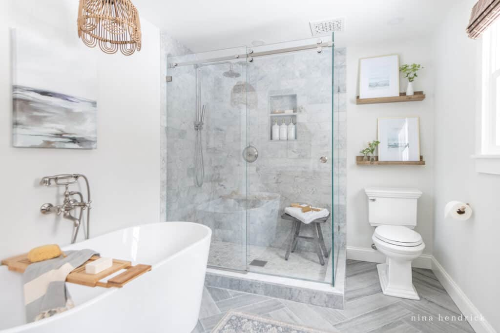Primary bathroom with glass shower surround and wood touches