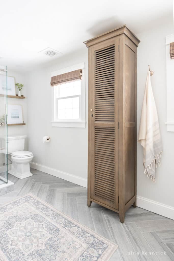 wood linen cabinet and a herringbone floor with a Ruggables rug