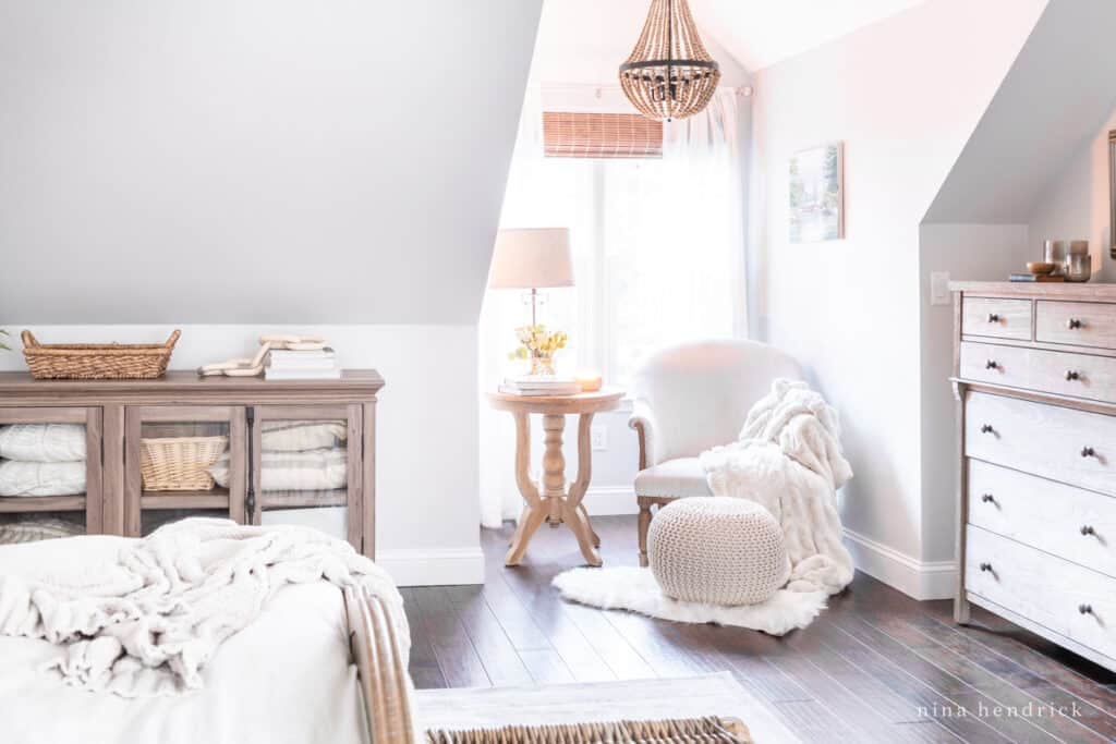A cozy reading nook with fur throws and a wood bead chandelier