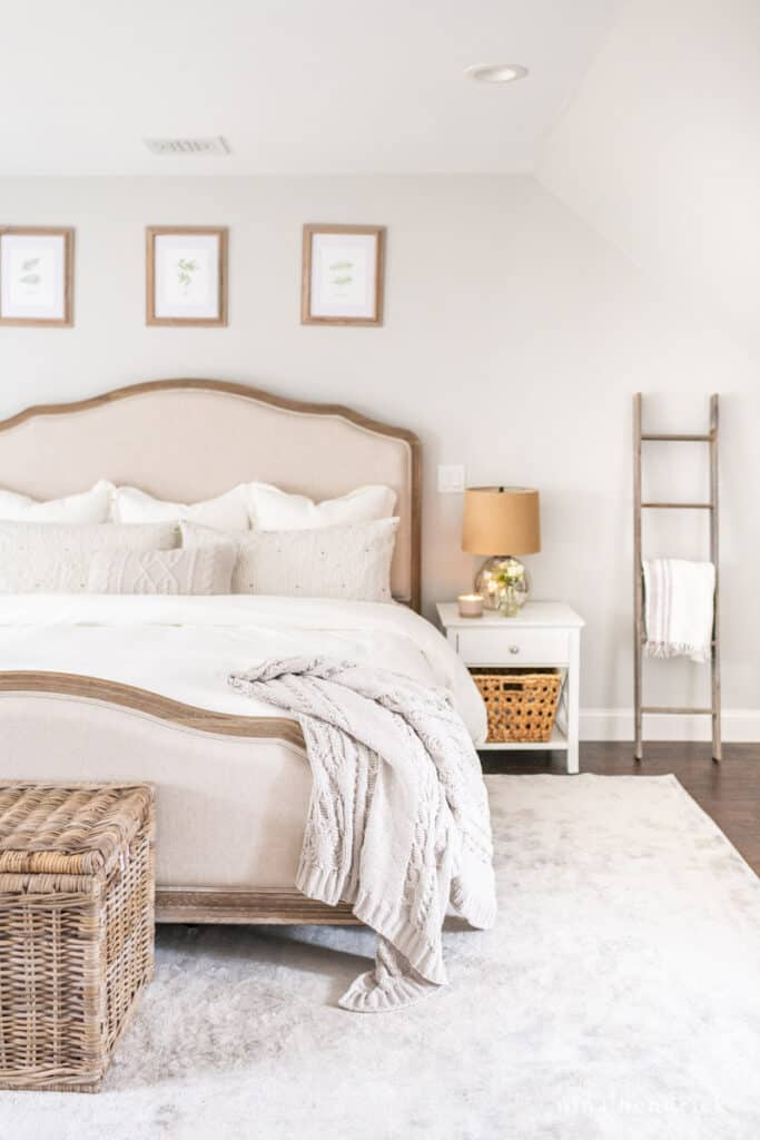 A cozy and neutral primary bedroom makeover with linens and a gorgeous vintage-style rug