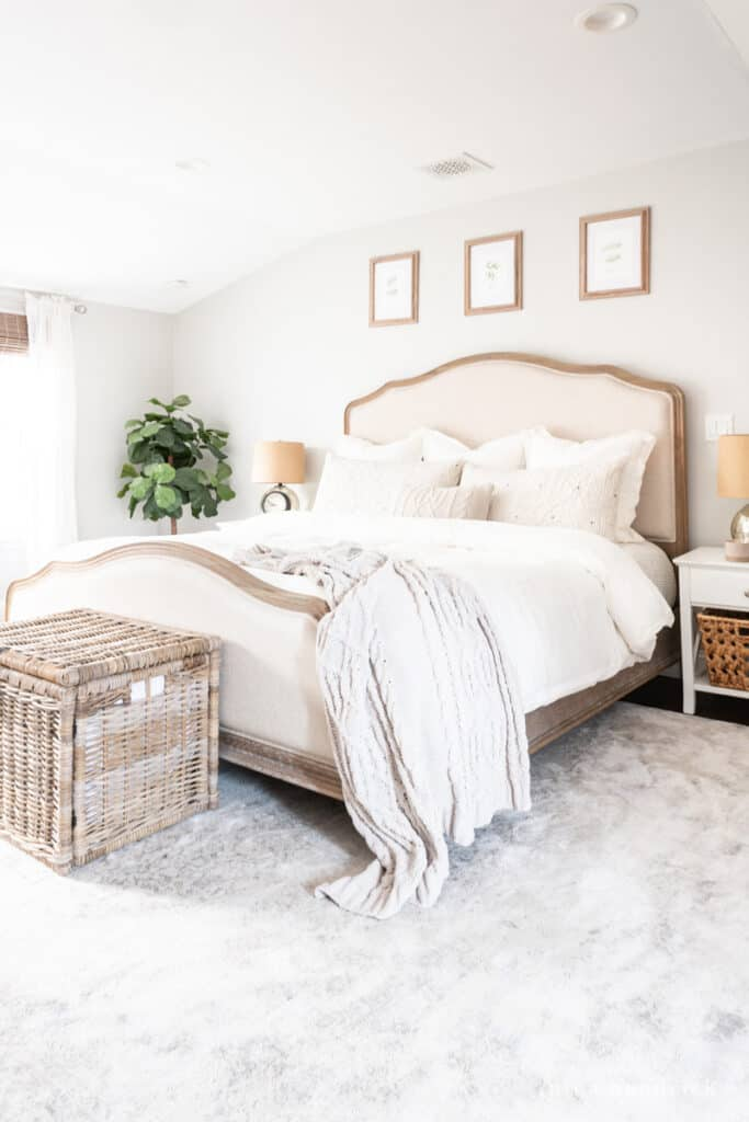 Primary bedroom makeover with neutral gray and white rug with a wood and upholstered bed.