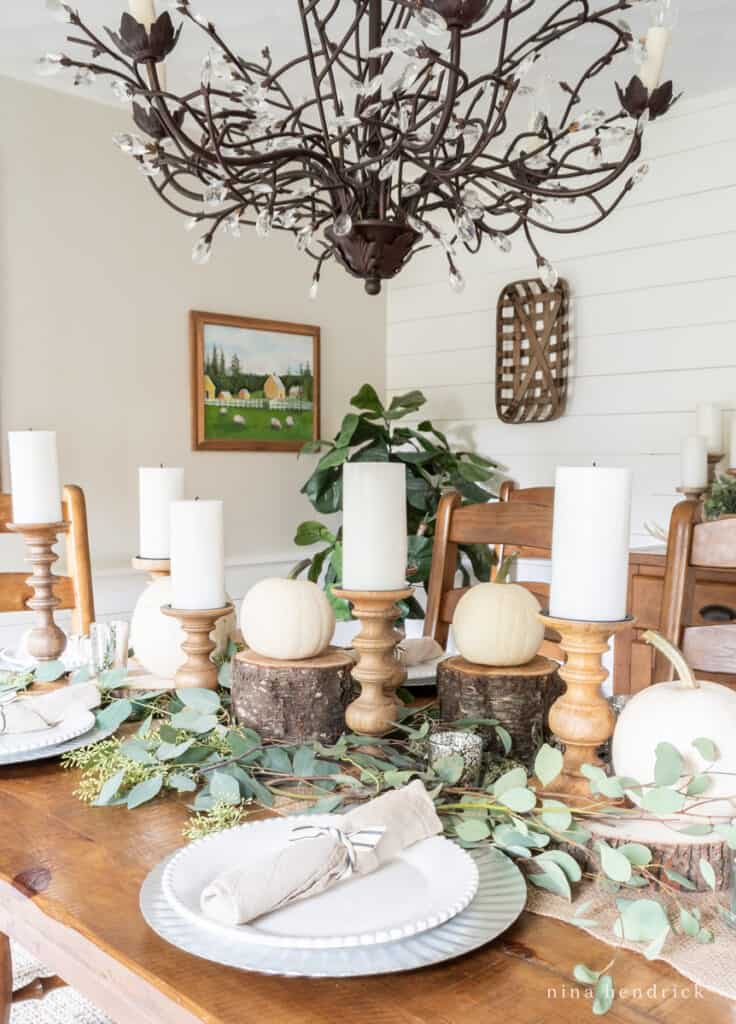 Neutral and rustic Thanksgiving centerpiece with wooden candle holders, wood slices, white pumpkins, and seeded eucalyptus.