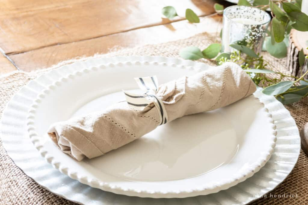 Thanksgiving place setting with bundled flatware in a beige linen napkin on a white plate