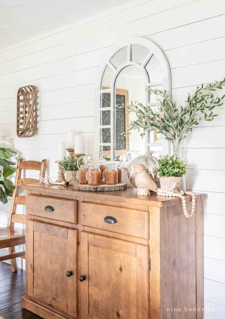 Warm pine buffet with a fall vignette and apple cider bar
