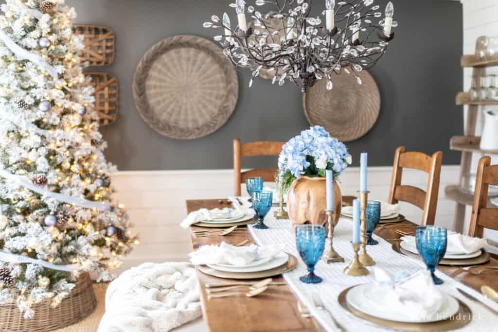 Simple blue Christmas tablescape with a neutral flocked tree
