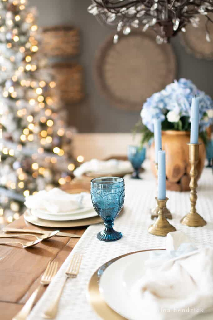 Blue candles and glassware on a Christmas tablescape