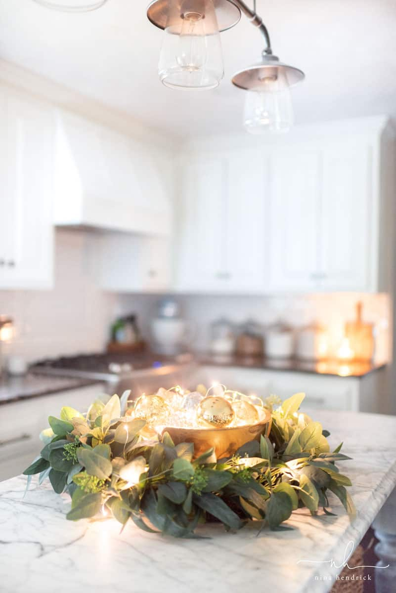 Simple Christmas Kitchen Decor| Decorate your kitchen for Christmas with simple greenery, wooden touches, and pretty golden lights for a classic but elegant theme.