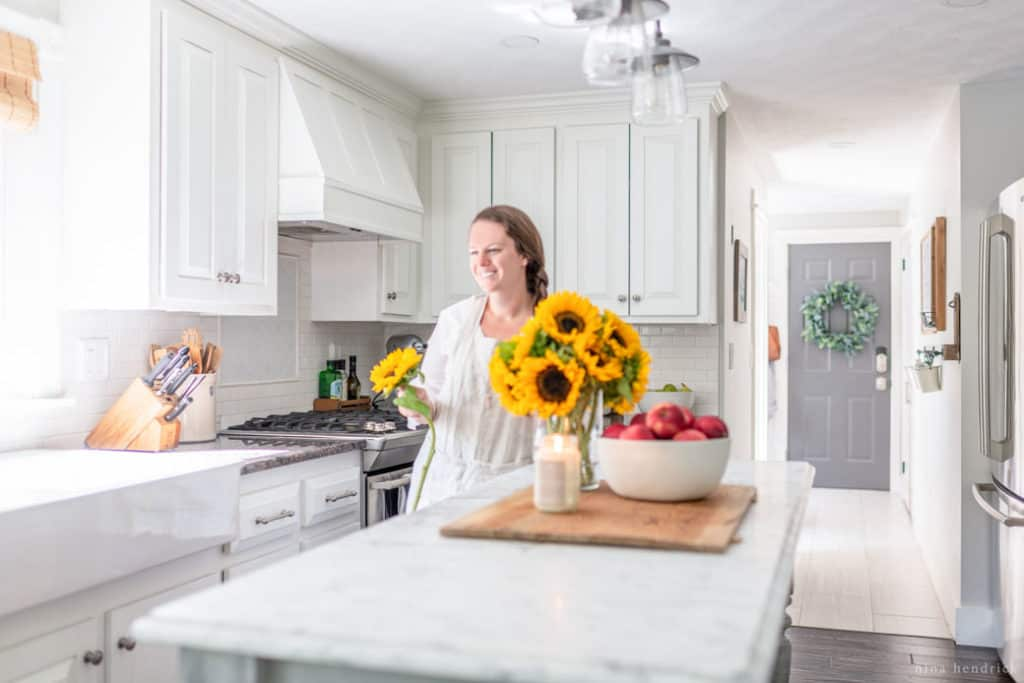 woman arranging sunflowers in white kitchen