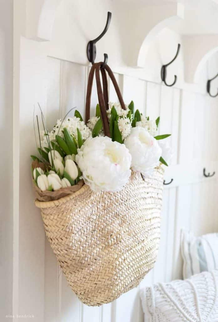 Spring Mudroom Decor | Beautiful flowers in a French market basket wait to be arranged on a hook in the mudroom.