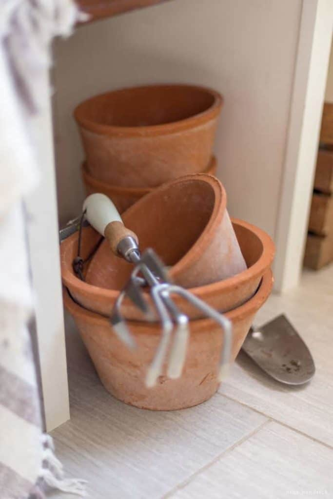 Spring Mudroom Decor | Rustic Terra Cotta pots sit in a mudroom waiting to be planted with Spring flowers.