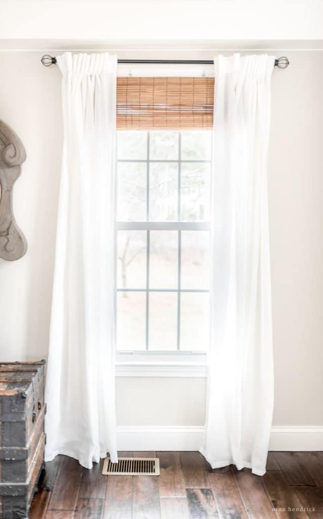 Stylish Budget Window Treatments | If you are looking to bring warmth and texture into your space, the combination of natural shades and light airy curtains is a perfect solution!