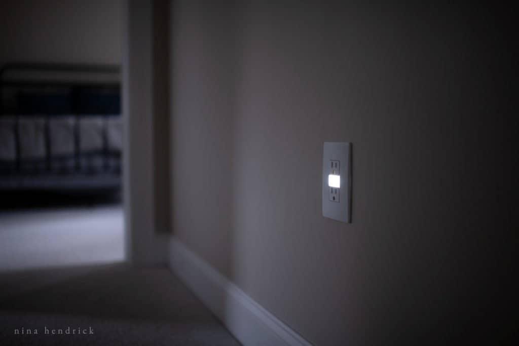Outlet with nightlight in dark hallway