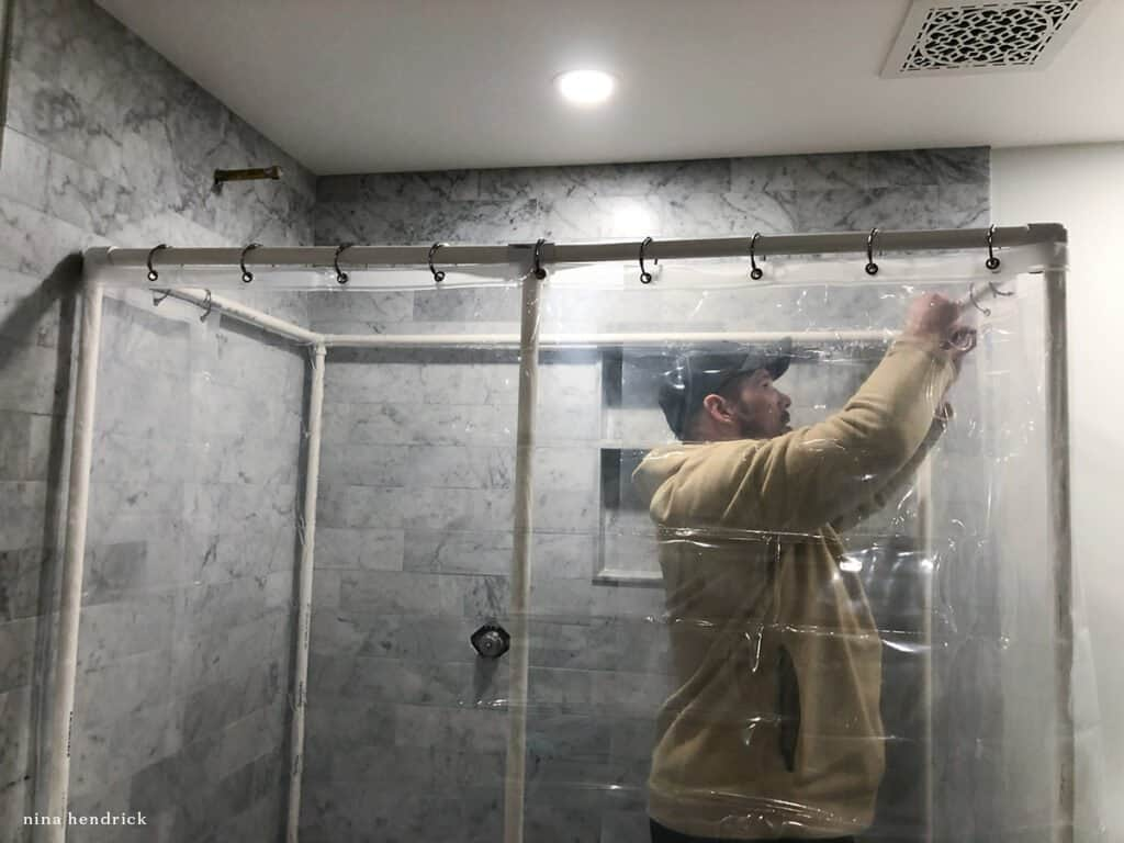 Man creating a PVC DIY Shower enclosure when bathroom improvement projects don't go according to plan.
